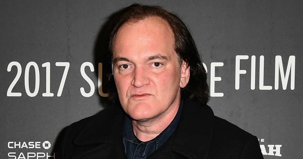 Tarantino ripreso in primo piano, capelli a mezzo collo, stempiato, sguardo allucinato.