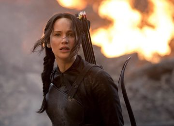 Hunger Games ha come attrice protagonista Jennifer Lawrence, qui in primo piano, di fronte ad un incendio