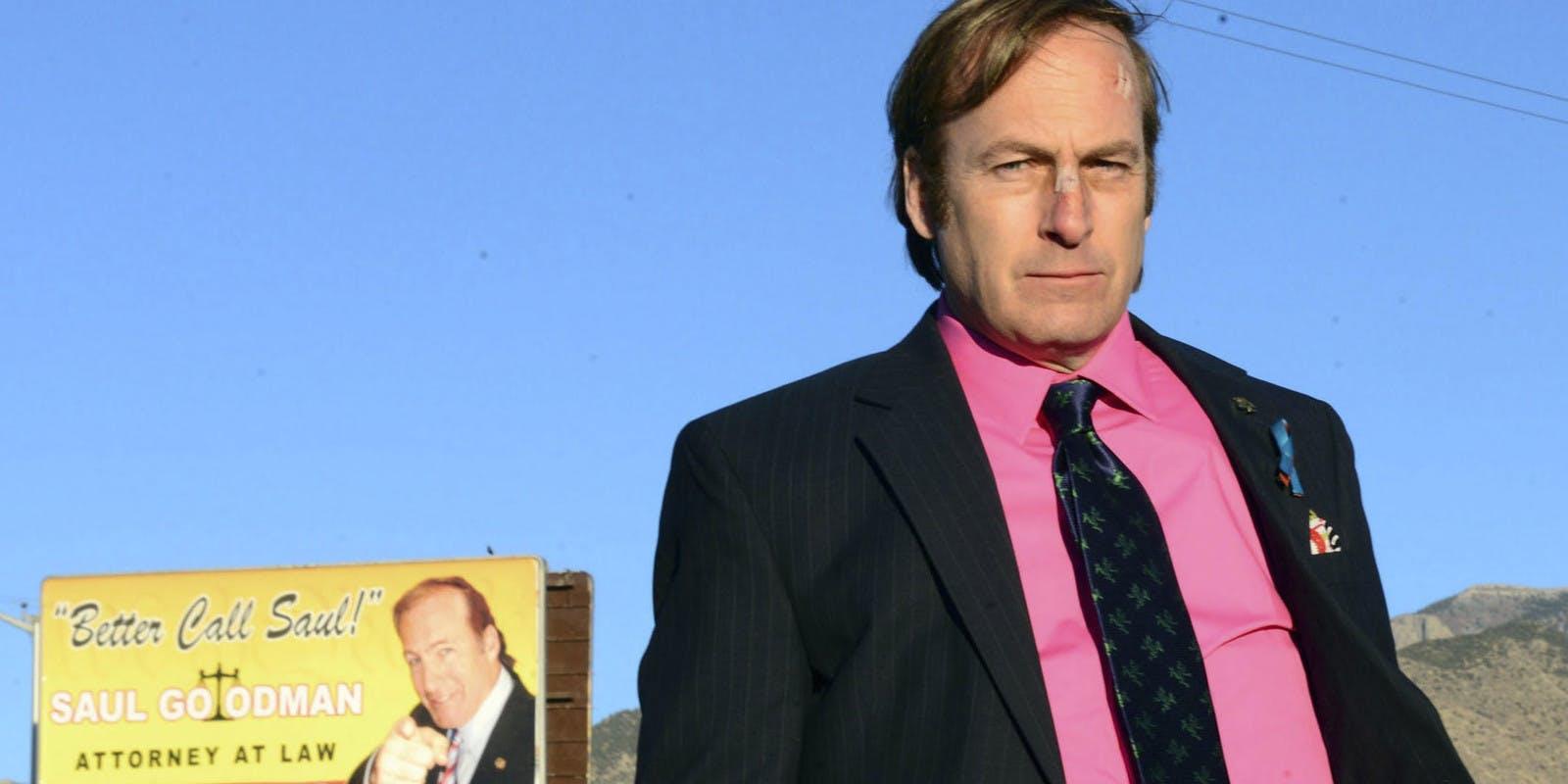 Saul Goodman coi cerotti in faccia di fronte al suo manifesto pubblicitario in cui grida Better Call Saul
