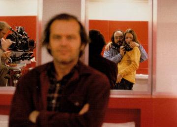 Stanley Kubrick e la figlia Vivian si fotografano davanti ad uno specchio sul set di Shining. In primo piano, uno sfocato Jack Nicholson.