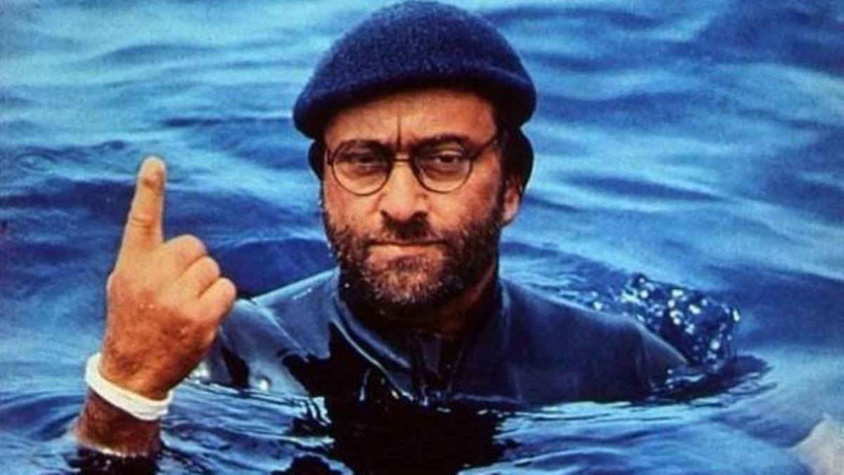 Lucio Dalla vestito col cappello, fa capolino dall'acqua del mare, con l'indice destro puntato verso l'alto.