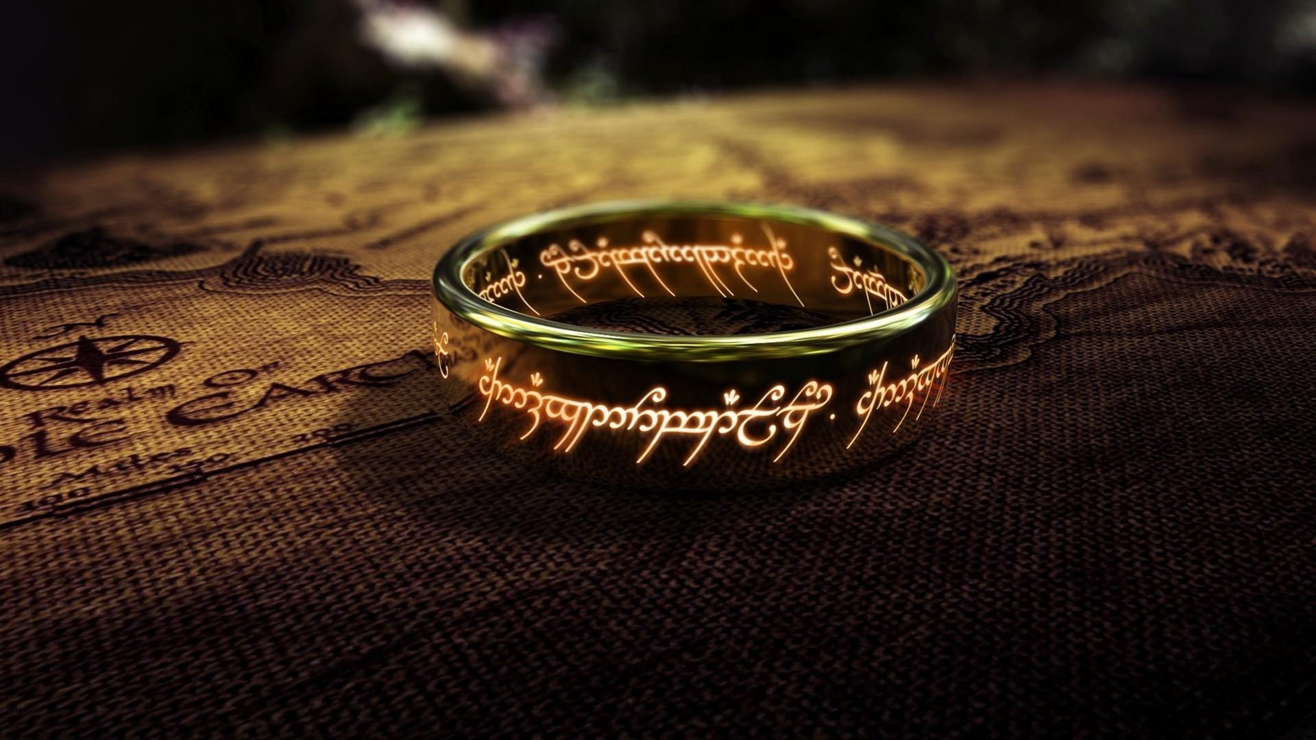 L'unico anello, oggetto principale di The Lord of the Rings, inquadrato con le scritte di fuoco lungo la fascia, adagiato su una cartina della Terra di Mezzo