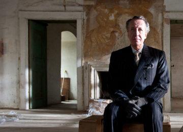 Geoffrey Rush sul set de La Migliore Offerta, seduto su un baule in una casa diroccata